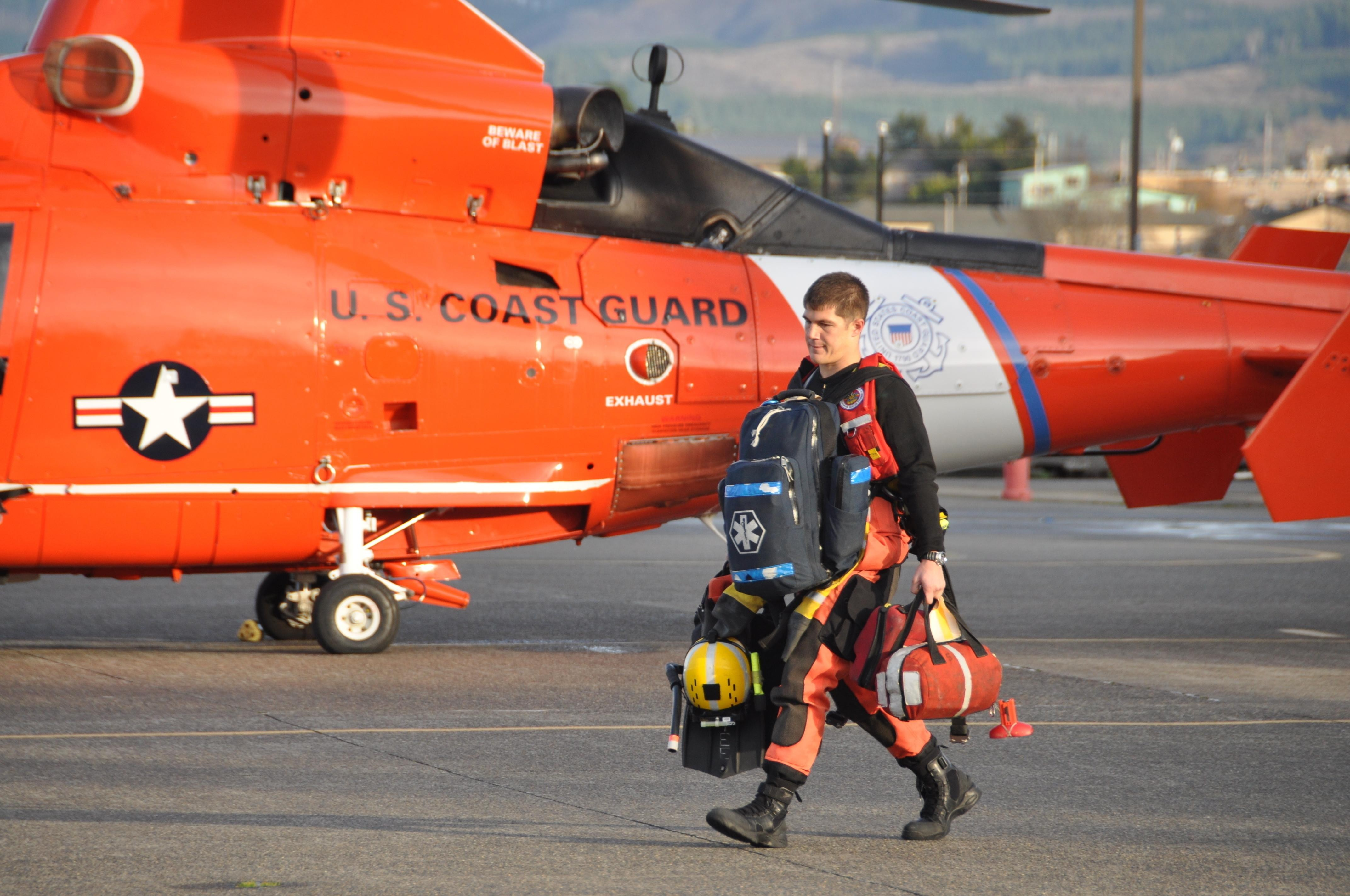 a coast guard rescue swimmer carries gear to an mh 65 dolphin helicopter before launching